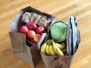Two grocery bags with apples, bananas, cabbage, bagels, and a baguette