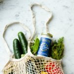 A netted bag full of groceries including produce and Tzatziki