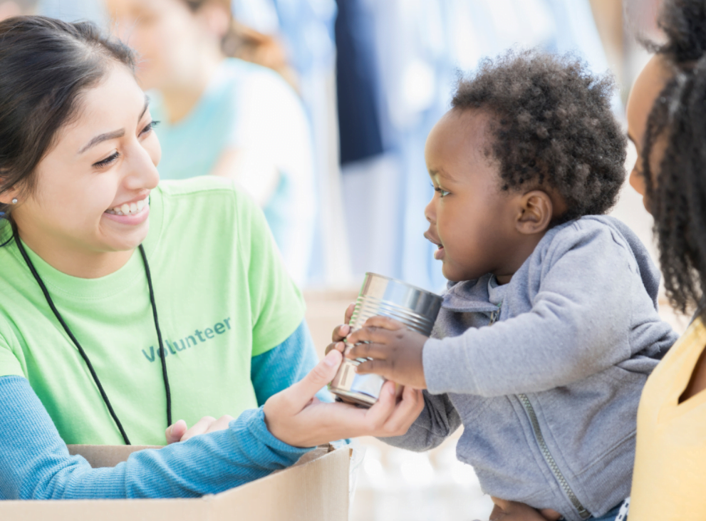 A volunteer helps a young child sip a glass of water in the Catholic Charities Food Pantry