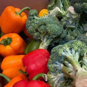 A close-up photo of a pile of vibrant bell peppers and broccoli