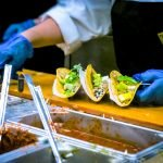 A person wearing gloves and dressing three tacos on a cafeteria line