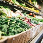 The vegetable aisle in a grocery store, featuring dark leafy greens