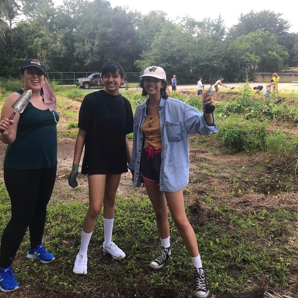 Three Gainesville Giving Garden volunteers standing together outdoors and smiling