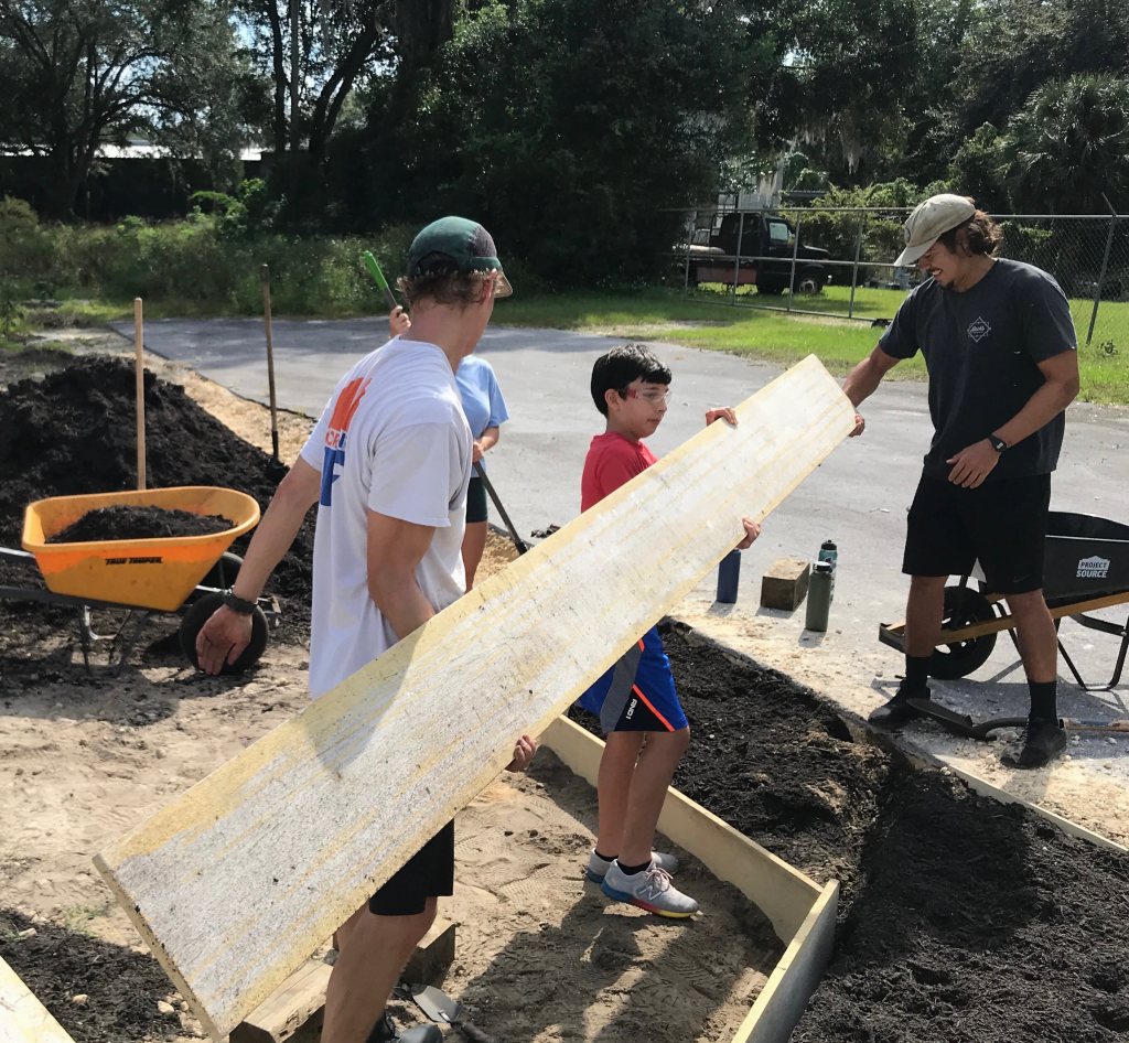 Three community members working together to build raised garden beds for the Gainesville Giving Garden